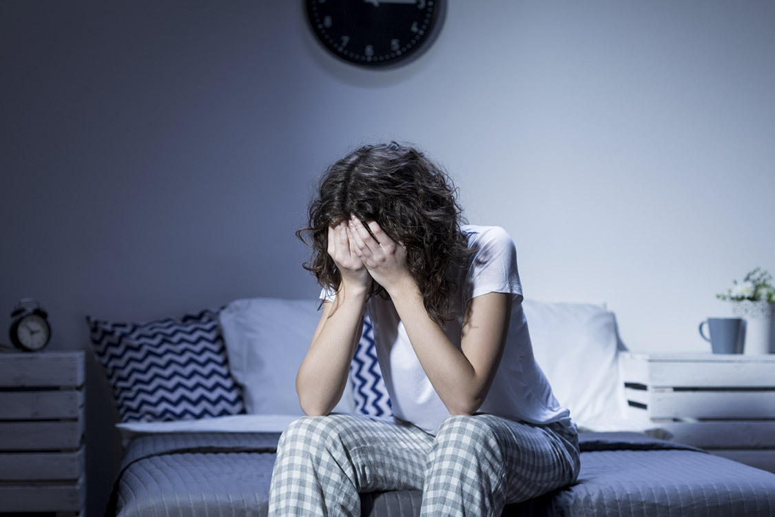 Depression and insomnia- young woman sitting on bed
